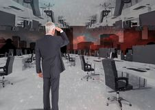 Businessman standing in inverted office with skyline. Digital composite of businessman standing in inverted office with skyline Stock Photo