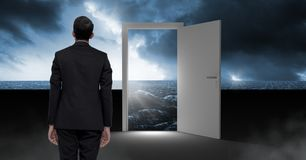 Businessman standing by open door with surreal dark sea glow and sky. Digital composite of Businessman standing by open door with surreal dark sea glow and sky Royalty Free Stock Photo