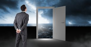Businessman standing by open door with surreal dark sea glow and sky. Digital composite of Businessman standing by open door with surreal dark sea glow and sky Royalty Free Stock Image