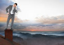 Businessman standing on Roof with chimney and misty colorful sky landscape Stock Photo