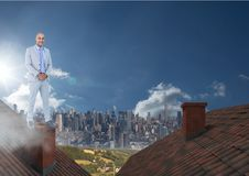 Businessman standing on Roofs with chimney and city. Digital composite of Businessman standing on Roofs with chimney and city Royalty Free Stock Photo