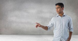 Businessman touching air in front of grey background Stock Photography