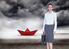 Businesswoman with briefcase and red paper boat in sea Stock Images