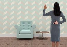 Businesswoman with fingers crossed in quirky wallpapered room with armchair. Digital composite of Businesswoman with fingers crossed in quirky wallpapered room Royalty Free Stock Photography