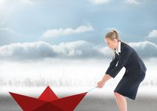 Businesswoman pulling paper boat with rope in city Stock Photo