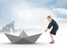 Businesswoman pulling paper boat with rope in city sky Stock Image