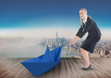 Businesswoman pulling paper boat with rope in city sky Royalty Free Stock Photos