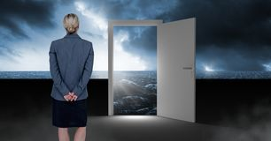 Businesswoman standing by open door with surreal dark sea glow and sky. Digital composite of Businesswoman standing by open door with surreal dark sea glow and Royalty Free Stock Photo