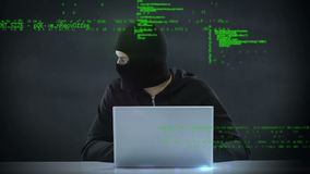 Hacker using a laptop. Digital composite of a Caucasian hacker looking left and right while using a laptop and foreground shows program codes stock footage
