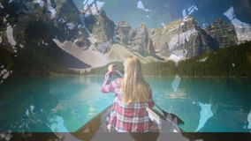 Woman kayaking in a lake. Digital composite of a Caucasian woman on a boat kayaking in a lake with a view of the mountains and background of silhouette of leaves stock footage