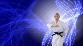 Woman doing karate. Digital composite of Caucasian woman doing karate with background of blue and white glowing lines stock video footage