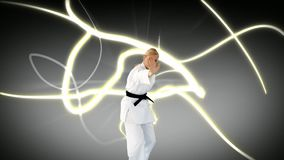 Woman doing karate. Digital composite of a Caucasian woman doing karate while glowing strings move in the background stock footage