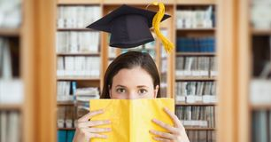 Composite image of woman with book and graduation hat stock photos