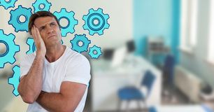 Confused man frowning and holding his head looking up in an office with cogs. Digital composite of Confused man frowning and holding his head looking up in an Stock Photo