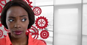 Confused woman in an office looking on the right with cogs. Digital composite of Confused woman in an office looking on the right with cogs Stock Photography