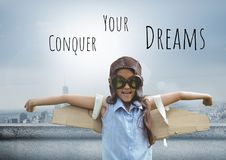 Conquer your dreams text and Pilot girl with wings over city background royalty free stock photography