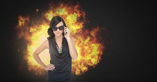 Cool woman in sunglasses with burning fire flames. Digital composite of Cool woman in sunglasses with burning fire flames royalty free stock photos