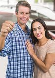 Couple Holding key in front of cars royalty free stock images