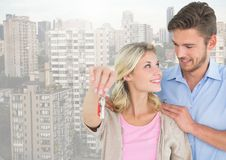 Couple Holding key in front of high rise apartments stock photography