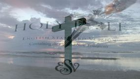 Cross in the shore. Digital composite of a cross by the shore with the sky and clouds and background shows holy bible and crucifix stock footage