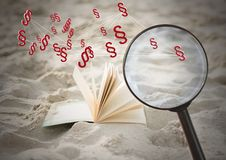 3D Magnifying glass over book with section symbol icons in sand. Digital composite of 3D Magnifying glass over book with section symbol icons in sand Stock Photo
