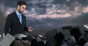 Dark bricks in pile with businessman holding phone. Digital composite of Dark bricks in pile with businessman holding phone stock photography