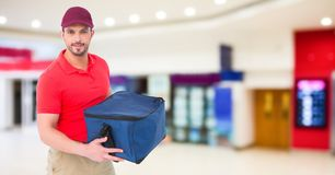 Delivery man against blurry shopping centre. Digital composite of Delivery man against blurry shopping centre Stock Photos