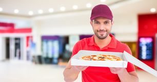 Delivery man with pizza against blurry shopping centre. Digital composite of Delivery man with pizza against blurry shopping centre Royalty Free Stock Image