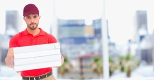 Delivery man with pizzas against blurry buildings royalty free stock photography