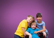 Disabled boy in wheelchair with friends with purple background stock photo