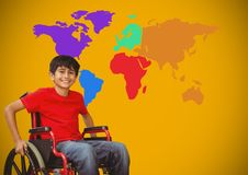 Disabled boy in wheelchair in front of colorful world map Royalty Free Stock Photos