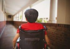 Disabled boy in wheelchair in school corridor stock images