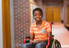 Disabled boy in wheelchair in school corridor royalty free stock image