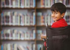 Disabled boy in wheelchair in school library royalty free stock image