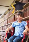 Disabled School girl in education library in wheelchair with graduation hat. Digital composite of Disabled School girl in education library in wheelchair with royalty free stock image