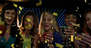 Friends celebrating and confetti 4k. Digital composite of a diverse group of female friends celebrating over drinks in a club while gold confetti falls in the stock video footage