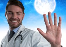 Doctor man touching air in front of moon. Digital composite of Doctor man touching air in front of moon Royalty Free Stock Photography