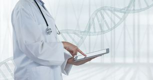 Doctor using a tablet with DNA strand. Digital composite of Doctor using a tablet with DNA strand stock photography