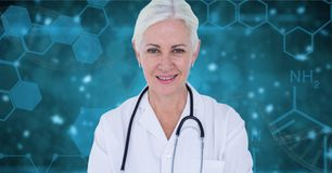 Doctor woman standing against blue background with medical interfaces stock image