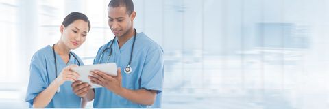 Doctors looking at a tablet against blue background royalty free stock photography
