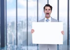Excited business man holding blank card in office Royalty Free Stock Images