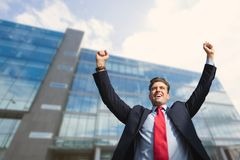 Excited business man standing against building background Stock Images