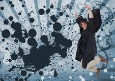 Excited young student man jumping and holding a diploma against blue splattered background. Digital composite of Excited young student man jumping and holding a Stock Images