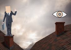 Eye icon and Businessman standing on Roofs with chimney and cardboard box on his head and dramatic l. Digital composite of Eye icon and Businessman standing on Royalty Free Stock Photography