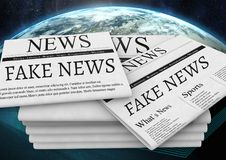 Fake news text on newspaper stack over planet earth world Royalty Free Stock Image