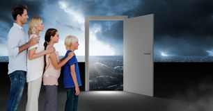 Family standing by open door with dark sea glow and surreal sky. Digital composite of Family standing by open door with dark sea glow and surreal sky Royalty Free Stock Photos