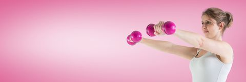 Fit athletic woman with pink background lifting weights stock images