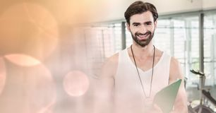 Fitness instructor smiling with bokeh in foreground. Digital composite of Fitness instructor smiling with bokeh in foreground Stock Photos