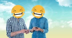 Digital composite of friends with laughing emojis on faces using smart phones Stock Image