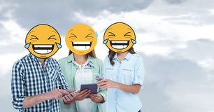 Digital composite of friends with laughing emojis using smart phones and digital tablet. Digital composite of Digital composite of friends with laughing emojis Stock Photo